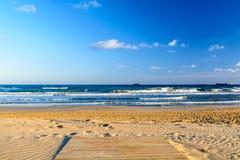 在沙滩的木背景的甲板与蓝天和海洋 在海浪顶部的白色泡沫在塔拉贡纳西班牙 免版税库存照片