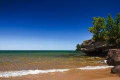在沙滩的清楚的蓝天与岩石海岸线 免版税图库摄影