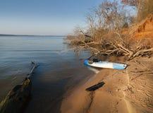 在沙滩的皮船与漂流木头 免版税图库摄影