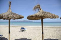 在沙滩的秸杆伞 免版税库存照片