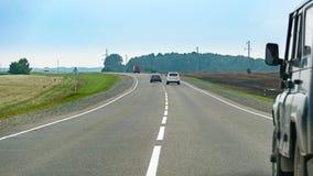 在沥青乡下路绕的汽车追逐通过领域 免版税库存图片