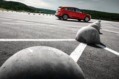 在沥青停车处的红色汽车在白天 免版税库存图片