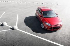 在沥青停车处的红色汽车逗留在白天 免版税库存图片