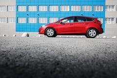 在沥青停车处的红色汽车 免版税库存照片
