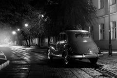 在沥青城市道路的老减速火箭的汽车逗留在多雨晚上 图库摄影