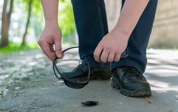 在沥青步行路站立并且培养下落的和残破的太阳镜的城市街道上的人的脚 图库摄影