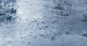 在沥青特写镜头的大雨下落 冷定调子 免版税库存图片