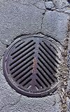 在沥青的下水道花格 图库摄影