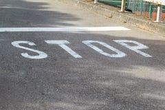 在沥青的停车牌 免版税库存图片