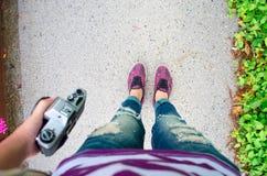 在沥青的妇女美好的腿在与紫色花的绿草附近 库存图片