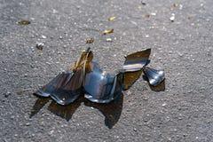 在沥青的残破的瓶 库存图片