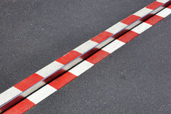 在沥青的红色和白色警告 免版税库存照片