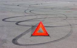 在沥青的警告三角和轮胎轨道 免版税库存照片