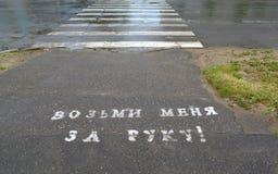 在沥青的题字用俄语用手采取我! ` 行人穿越道 免版税库存照片