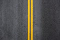在沥青的黄色双重实线 免版税库存照片