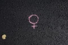 在沥青背景的白垩画的男女平等的标志,在妇女` s手上 库存图片