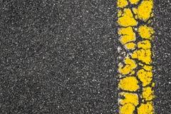 在沥青背景的黄色路标条纹 库存照片