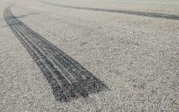 在柏油路的被烧的橡胶轮胎轨道 库存照片