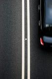 在沥青路的双黄线分切器与汽车 免版税库存图片