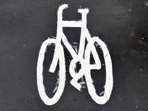 在沥青路面的被绘的自行车标志 免版税库存图片
