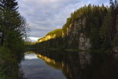 在河上的岩石在晚上点燃 免版税图库摄影