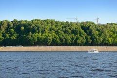 在河下的快速汽艇航行沿与一个绿色森林和塔吊的一个具体堤防 免版税库存图片
