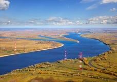 在河之上的输电线运行 免版税库存照片