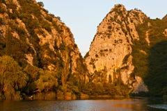 在河分开的日落附近的峡谷 免版税库存照片