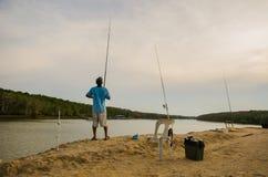 在河前面的人渔晚上 库存照片