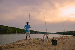 在河前面的人渔晚上 免版税库存照片