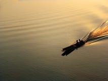 在河剪影的马达船 库存照片