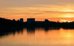 在河反映的城市在日落 免版税库存图片