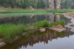 在河反映的岩石海岸 库存照片