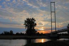 在河和日出上的桥梁 免版税库存图片