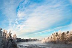 在河和森林之上的云彩 免版税库存照片