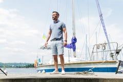 在河塑造年轻人在背景的画象和游艇 有游艇的水手 反对游艇的人画象有被折叠的风帆的 免版税图库摄影