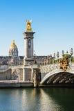 在河塞纳河的Pont亚历山大III桥梁有旅馆des的Invali 免版税图库摄影