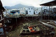 在河小河的被放弃的小船与渔夫的生锈的金属建筑在村庄 免版税库存图片