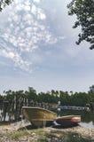 在河岸和多云天空搁浅的渔夫小船美好的海景风景 图库摄影