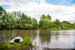 在河岸的一条灰色可膨胀的小船在春天和夏天 免版税库存照片
