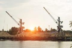 在河岸的两端的起重机生产河沙子,日落,驳船 库存图片