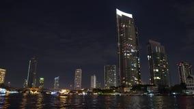 在河岸的公司大厦在大都会 夜间,从办公室窗口的光 股票视频