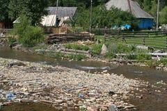 在河岸的垃圾在村庄附近 库存照片
