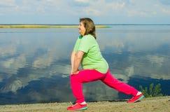 在河岸的妇女锻炼 免版税图库摄影