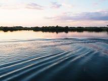 在河岸的日落场面有水波纹的,反射和 库存照片