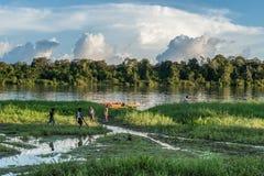 在河岸的未知的儿童游戏,在村庄附近 日落,天的结尾 2012年6月26日在村庄,新几内亚,印度尼西亚 免版税库存图片