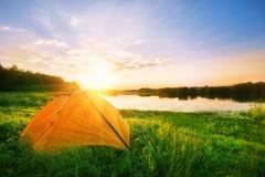 在河岸的橙色帐篷 免版税库存图片