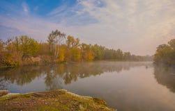 在河岸的秋天木头 免版税图库摄影