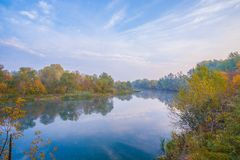 在河岸的秋天木头 免版税库存图片