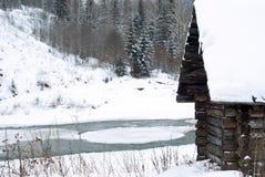 在河岸的老日志小屋冬天风景的 免版税库存图片